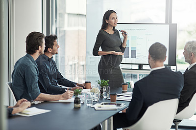 Buy stock photo Shot of a pregnant businesswoman giving a presentation on a monitor to colleagues in an boardroom