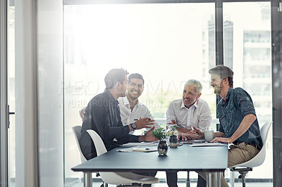 Buy stock photo Shot of a group of businessmen having a meeting around a table in an office