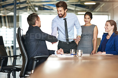 Buy stock photo Shot of two businesspeople shaking hands while in a meeting with colleagues in a boardroom