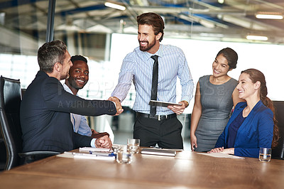 Buy stock photo Shot of two colleagues shaking hands while in a meeting with colleagues in a boardroom