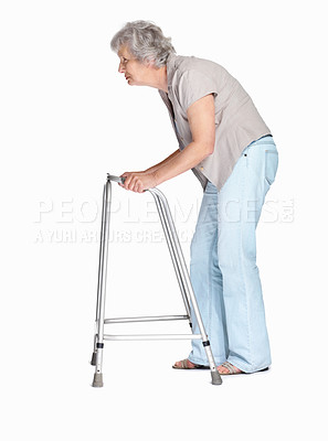 Buy stock photo Full length of a disabled mature woman walking while using Zimmer isolated against white