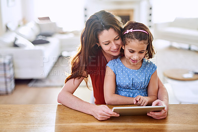 Buy stock photo Cropped shot of mother and daughter using a digital tablet together at home