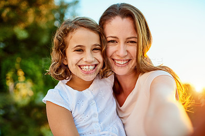 Buy stock photo Portrait of a mother and daughter taking a selfie together outside
