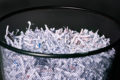 Buy stock photo Studio shot of shredded paper in a dustbin against a black background