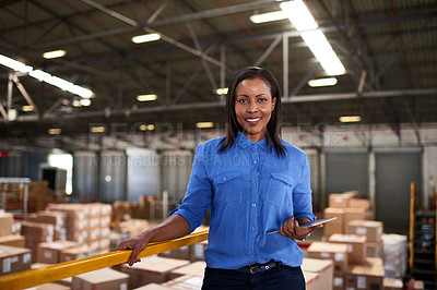 Buy stock photo Portrait of a smiling worker holding a digital tablet while standing in a large warehouse full of boxes