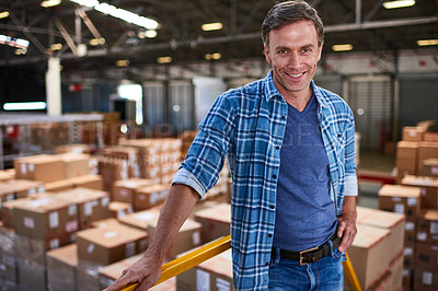 Buy stock photo Portrait of a smiling worker standing in a large warehouse full of boxes