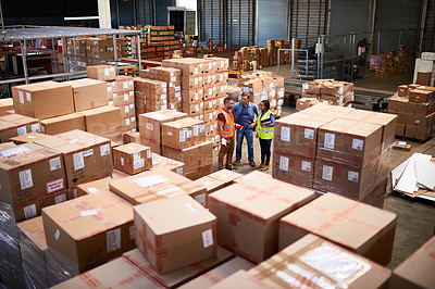 Buy stock photo Shot of people at work in a large warehouse full of boxes