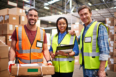 Buy stock photo Portrait of a group of smiling coworkers standing in a large warehouse full of boxes