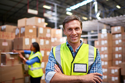 Buy stock photo Portrait of a worker standing in a large warehouse full of boxes with a colleague in the background