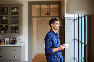 Buy stock photo Shot of a young man drinking a coffee while looking through his kitchen window