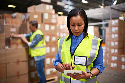 Buy stock photo Shot of a worker using a digital tablet in a large warehouse full of boxes with a colleague in the background