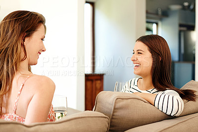 Buy stock photo Shot of two young friends talking and drinking wine while relaxing on the sofa