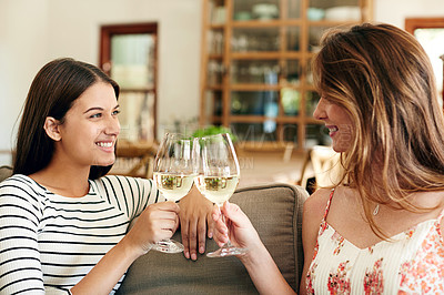 Buy stock photo Shot of two young friends toasting with wine while relaxing on the sofa