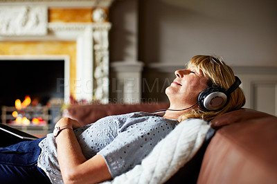 Buy stock photo Shot of a mature woman lying on her sofa listening to music on headphones with a fire in the background