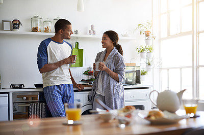 Buy stock photo Shot of a young couple talking together and drinking coffee in their kitchen in the morning