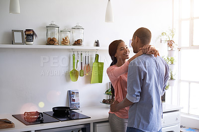 Buy stock photo Shot of a young couple talking while standing arm in arm together in their kitchen