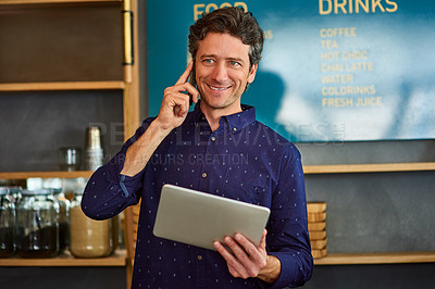 Buy stock photo Shot of a man talking on the phone and using a digital tablet while standing in his cafe