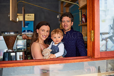 Buy stock photo Portrait of a smiling couple and their little girl standing at the window of their bakery
