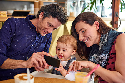Buy stock photo Shot of a mother and father showing their baby girl photos on a phone while sitting in a cafe