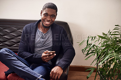 Buy stock photo Portrait of a smiling young man sitting in an office using a cellphone