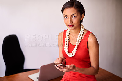 Buy stock photo Portrait of a young woman using a cellphone while sitting on her desk in an office