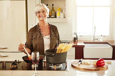 Buy stock photo Shot of a senior woman cooking in her kitchen