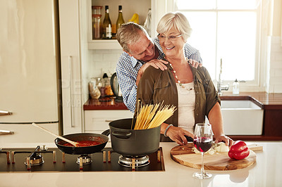 Buy stock photo Shot of an affectionate couple preparing a meal in the kitchen