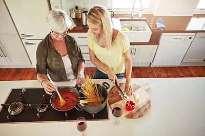 Buy stock photo Shot of a senior woman and her daughter cooking in the kitchen