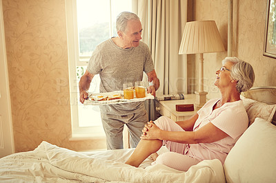 Buy stock photo Shot of a senior man bringing breakfast in bed to his wife