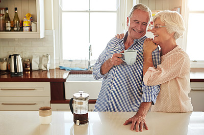 Buy stock photo Shot of an affectionate senior couple in the kitchen