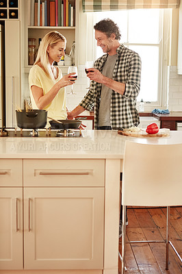 Buy stock photo Shot of a couple enjoying a glass of wine while cooking supper