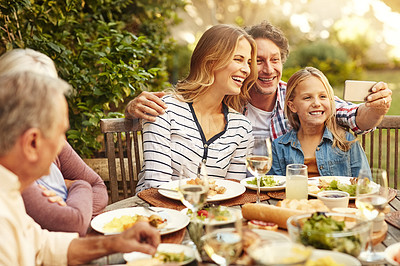 Buy stock photo Shot of a happy family taking a selfie together at an outdoor lunch