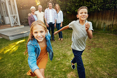 Buy stock photo Shot of a young brother and sister playing togther in the yard with their family in the background
