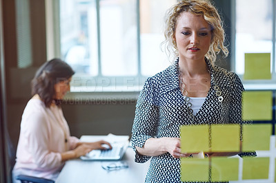 Buy stock photo Shot of a businesswoman reading adhesive notes on a glass wall with a colleague in the background