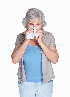 Buy stock photo Portrait of an allergic mature female using a paper tissue isolated against white
