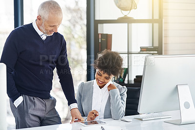 Buy stock photo Shot of a mature businessman showing his colleague something on a tablet