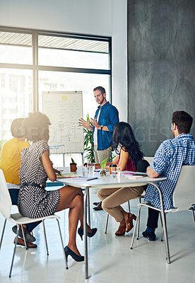 Buy stock photo Shot of a businessman giving a presentation to his colleagues in a modern office