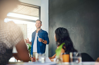 Buy stock photo Cropped shot of a businessman giving a presentation to his colleagues in a modern office