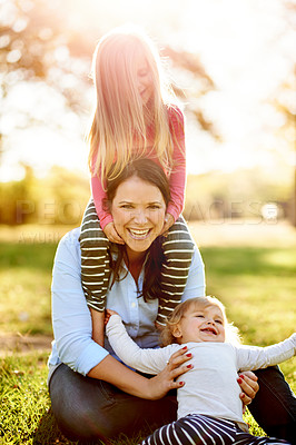 Buy stock photo Portrait of a mother and her young daughters playing together at the park