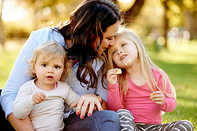 Buy stock photo Shot of a mother and her young daughters spending time together at the park