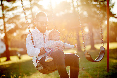 Buy stock photo Cropped shot of a father and daughter on a swing in the park