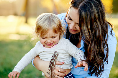 Buy stock photo Shot of a mother and her young daughter playing with a feather at the park