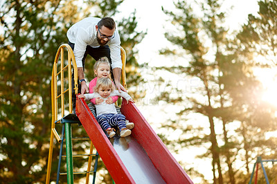 Buy stock photo Full length shot of a father and his two daughters on a slide in the park