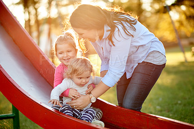 Buy stock photo Cropped shot of a mother and her two daughters on a slide in the park
