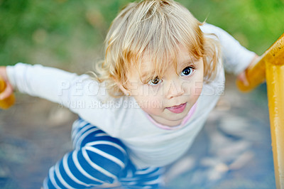 Buy stock photo Shot of an adorable little girl playing in a playground