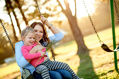 Buy stock photo Cropped shot of a mother and daughter on a swing in the park
