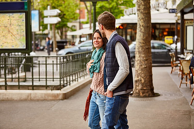 Buy stock photo Shot of a young couple enjoying the day together walking through the the city