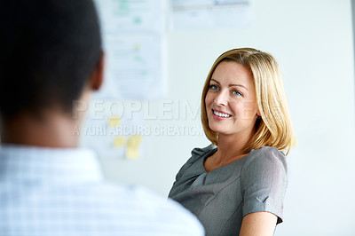 Buy stock photo Shot of a smiling businesswoman talking to a colleague in an office