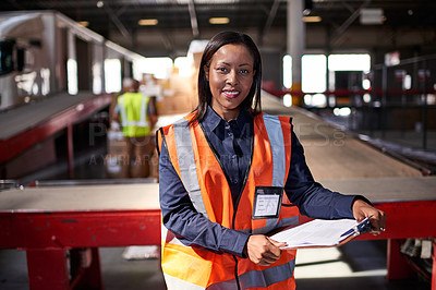 Buy stock photo Portrait of a warehouse manager holding a clipboard with workers in the background
