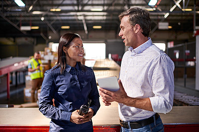 Buy stock photo Shot of two colleagues talking over a digital tablet while standing in a large warehouse